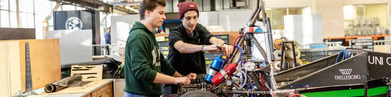 Two students working on the Formula Student racing car in the Leeds Gryphon Racing workshop.