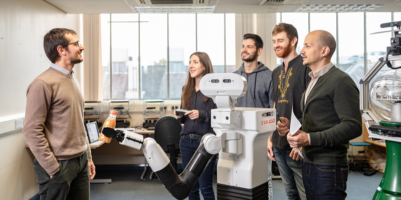 Dr Matteo Leonetti and PhD students with TiaGO robot