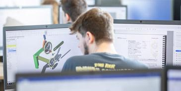 A student in front of two computer screens using CAD modelling software.