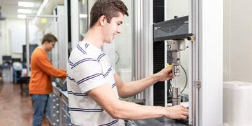 A student operating one of the tensile testing machines in the School of Mechanical Engineering.