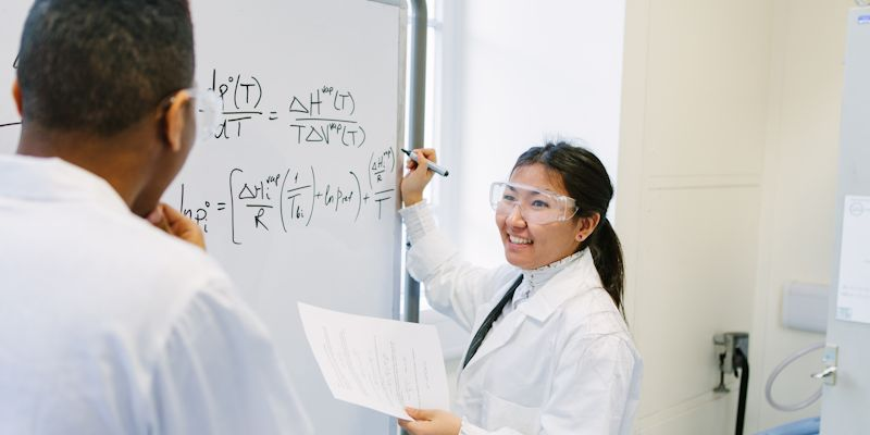 people in lab coat working on a problem on a white board