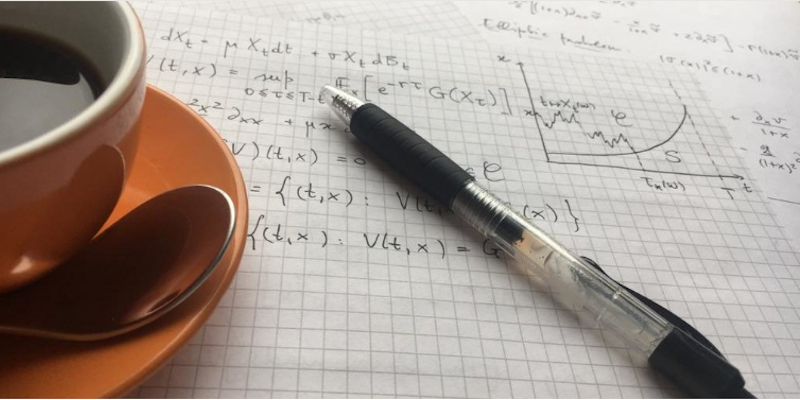 Cup of coffee on a a maths notebook on which there are formulas written