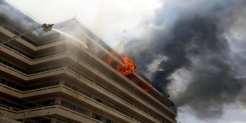 Flames coming out of top floor apartment in tower block