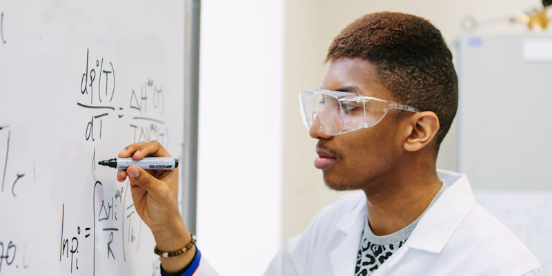 Male UG student writing on whiteboard in chemical engineering teaching lab