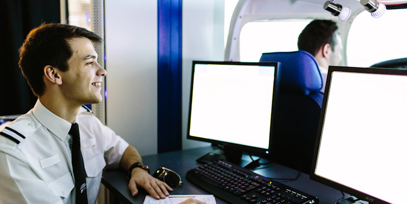 Aviation project work, male student looking at screen behind flight sim
