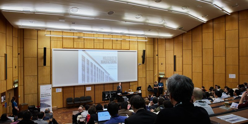 Lecture theatre seen from the last row, with attendees listening to a seminar