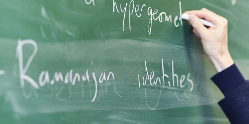 A hand writing on a chalkboard during a Centre for Doctoral Training lecture