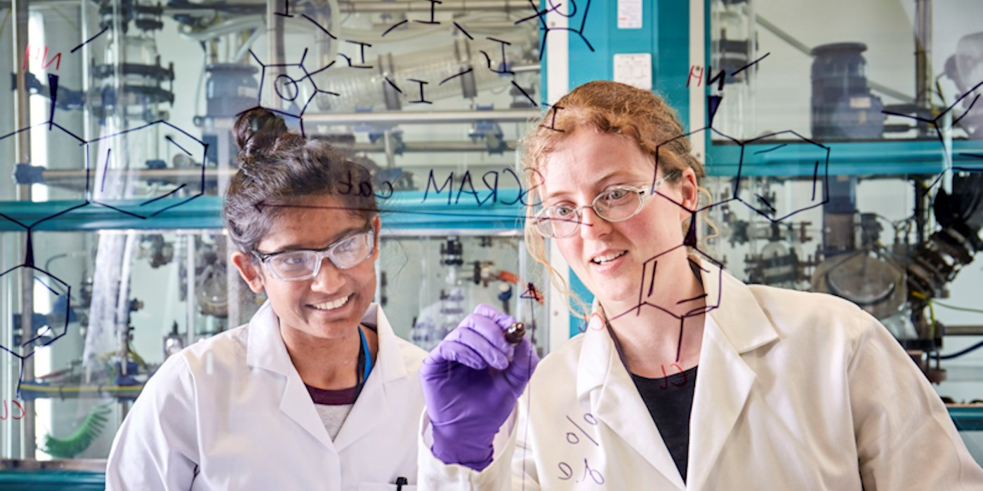 Two female researchers writing chemical formulas on a transparent screen