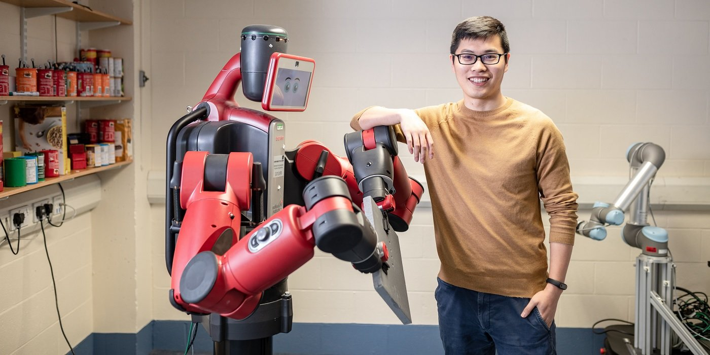 Student posing with Baxter robot
