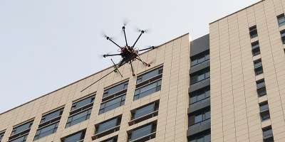 A drone flying by a building