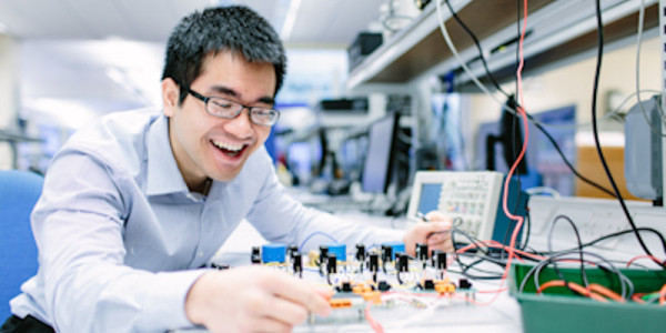 Male UG elec student with circuit board in basement lab b55