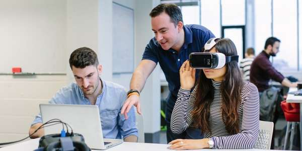 Three Computing students, one using VR