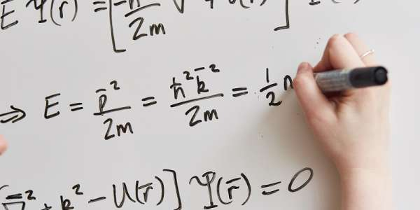 Equations written on a whiteboard, representing theoretical physics research