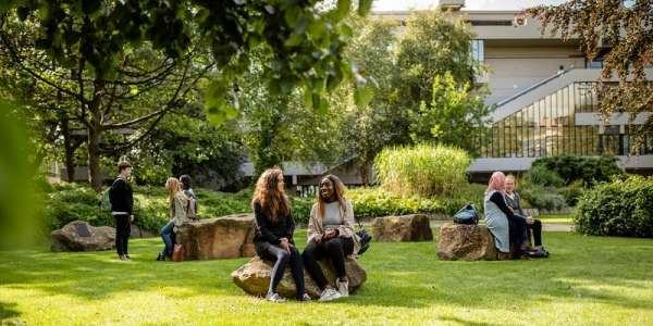 Students sitting in green space at the University of Leeds